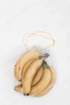Bananas frescas amarelas em sacos ecológicos naturais costurando de tecido de malha