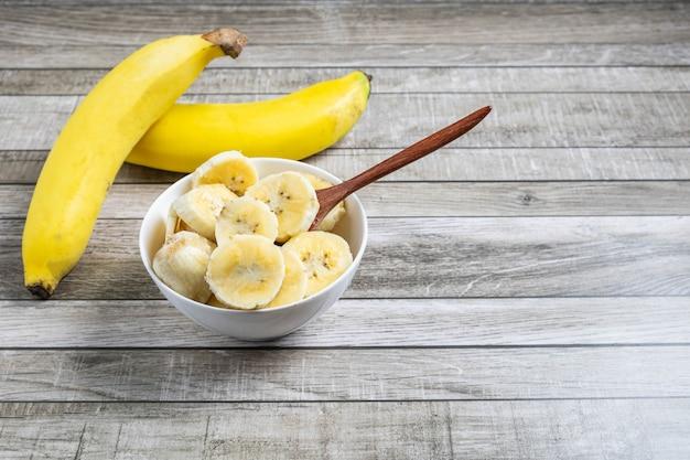 Bananas frescas e bananas cortadas em pedaços em uma tigela para a saúde na mesa.