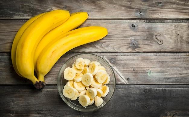 Bananas frescas e fatias de banana em uma tigela de vidro. sobre um fundo de madeira.
