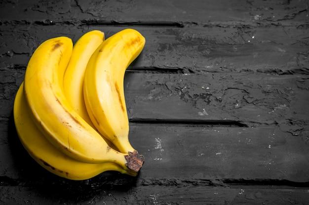 Bananas frescas inteiras. sobre fundo preto rústico.