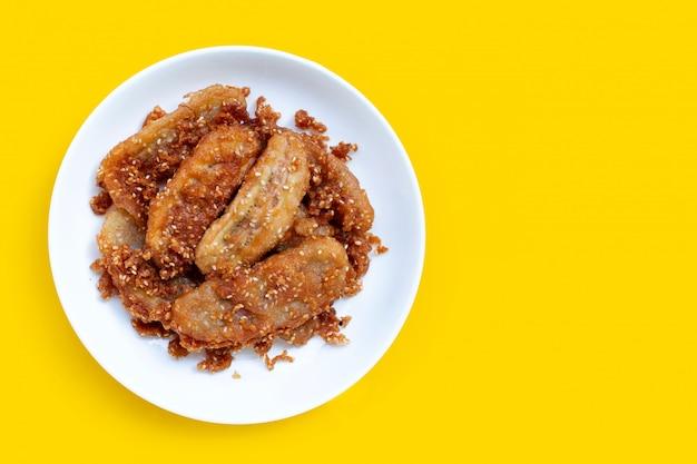 Bananas fritas com sementes de gergelim na placa redonda cerâmica branca sobre fundo amarelo.