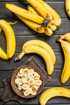 Bananas inteiras e rodelas de banana. sobre fundo preto rústico.