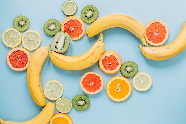 Bananas inteiras perto de frutas fatiadas