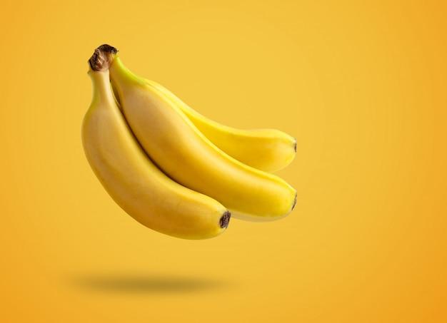 Bananas levitando sobre fundo amarelo, conceito de verão, espaço de cópia