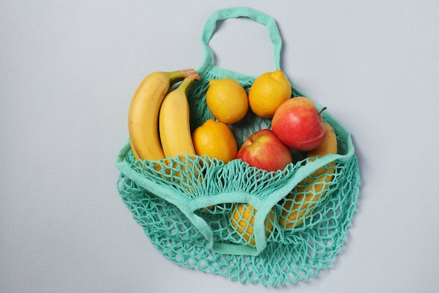 Bananas maduras amarelas, limões e maçãs em uma sacola de malha de barbante reutilizável