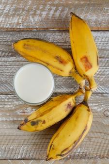 Bananas maduras com leite na madeira,