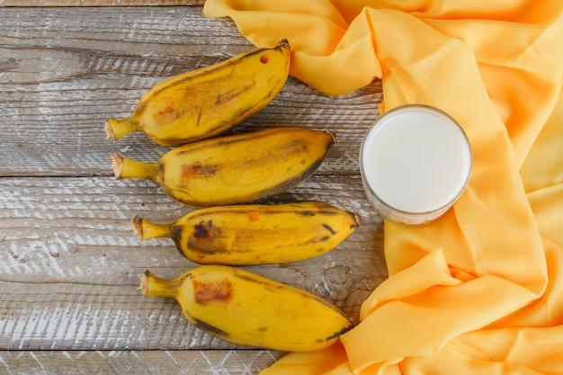 Bananas maduras com leite plano deitado em madeira e tecido