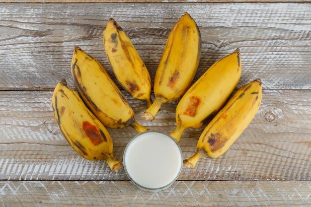 Bananas maduras com leite plano deitado sobre uma madeira
