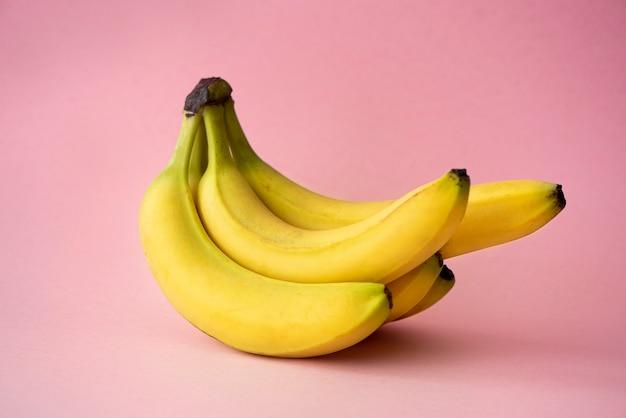 Bananas maduras grandes amarelas em um fundo rosa