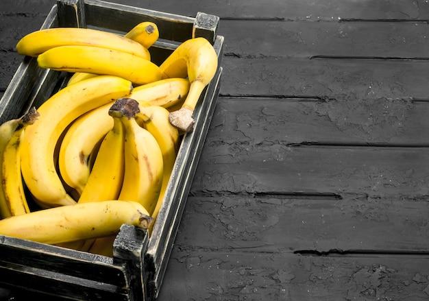Bananas na caixa preta. sobre fundo preto rústico.