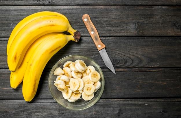 Bananas perfumadas e fatias de banana em uma tigela de vidro com uma faca. sobre um fundo preto de madeira.