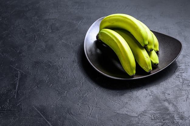 Bananas verdes em um prato. fundo preto. vista do topo. espaço para texto. fruta tropical