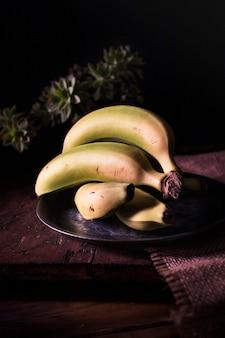 Bananas verdes em um prato na mesa da cozinha