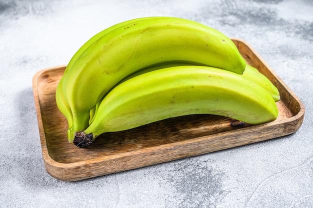 Bananas verdes em uma bandeja de madeira. fundo cinza. vista do topo. fruta tropical