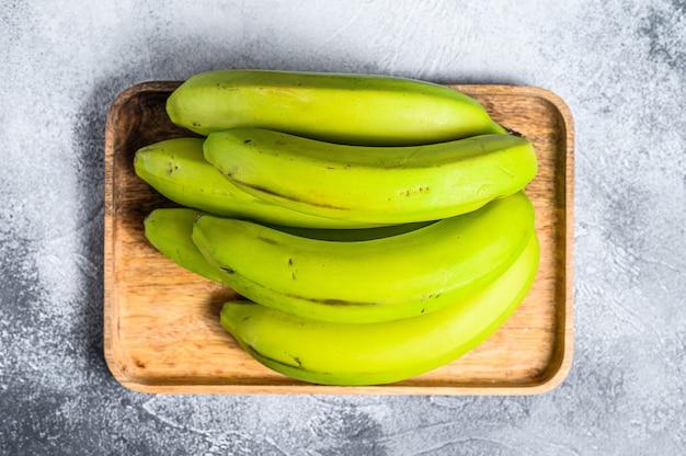 Bananas verdes em uma bandeja de madeira. vista do topo. fruta tropical