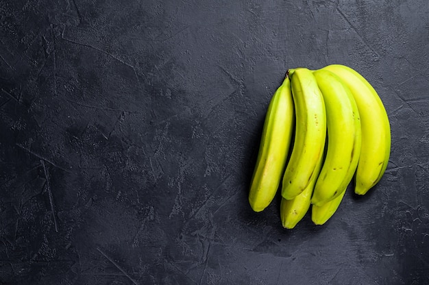 Bananas verdes. fundo preto. vista do topo. espaço para texto
