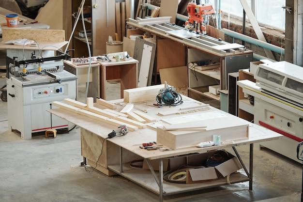Bancada de trabalho de operário de fábrica de móveis com peças de madeira, ferramentas elétricas e outras coisas cercadas por vários equipamentos