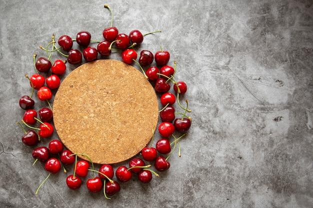 Bancada em mármore, suporte de cortiça para frutas quentes e cerejas. temporada de verão, colheita de frutas, geléia, compotas, lugar para inscrições