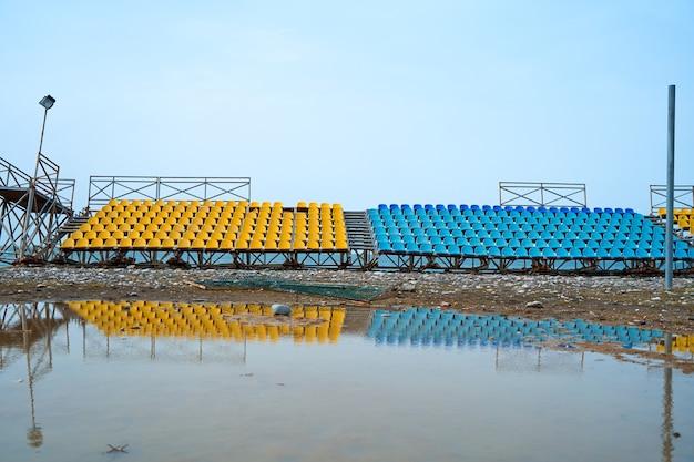 Bancadas desertas de um pequeno campo de esportes na praia em um dia chuvoso.