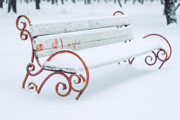 Banco coberto de neve com o símbolo do coração no parque da cidade