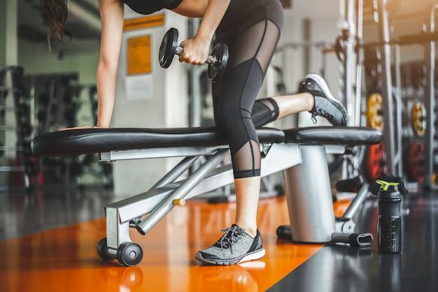 Banco da jovem mulher que pressiona com pesos no gym da aptidão. tríceps de trabalho e levantamento de peso no peito.