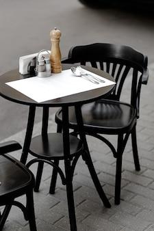 Banco de jantar ao ar livre com acessórios de mesa de restaurante.