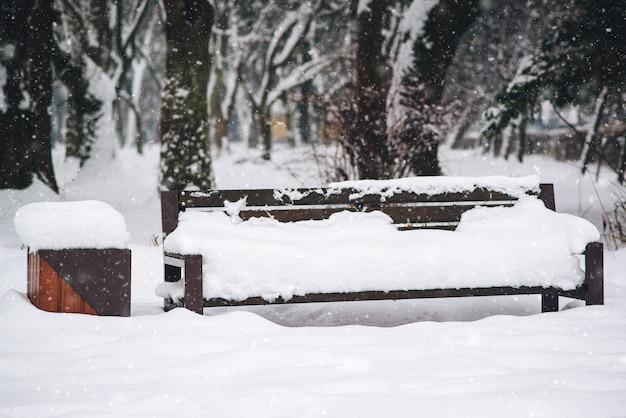 Banco de jardim coberto por neve forte