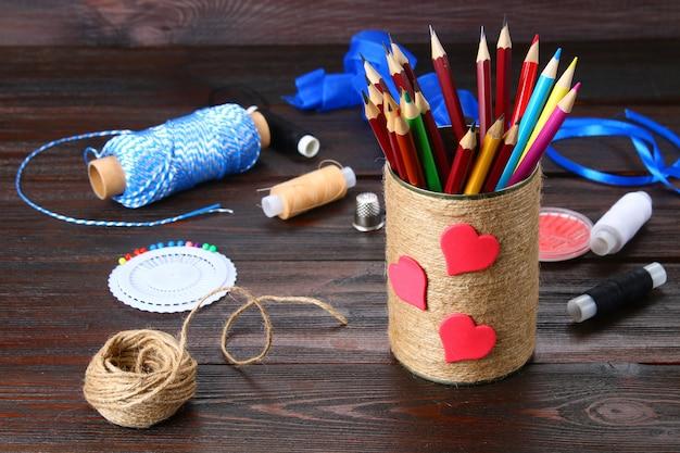Banco de lápis com corações embrulhados com barbante em uma mesa de madeira. feito à mão.