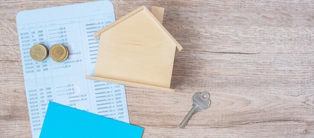 Banco de livro com modelo de casa e chave na mesa de madeira. financeiro, dinheiro, refinanciar, imóveis e novo conceito de aprimorar