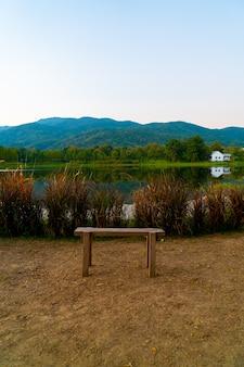 Banco de madeira com belo lago em chiang mai, com montanha florestada e céu crepuscular na tailândia.