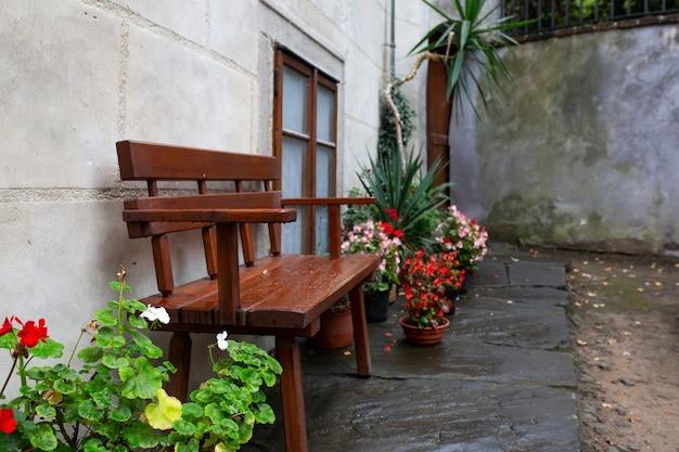 Banco de madeira com canteiros de flores no parque após a chuva