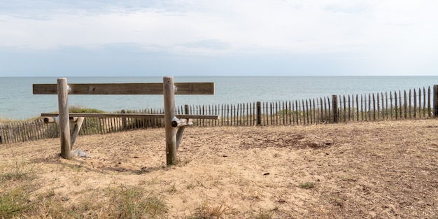 Banco de madeira da vista traseira vazio na costa atlântica em jard sur mer vendee france na bandeira do molde da bandeira da web
