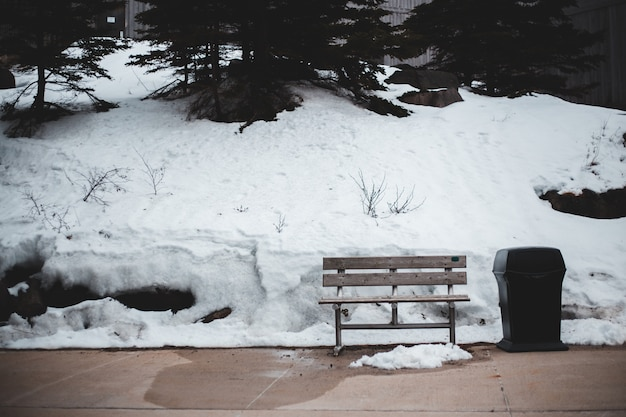 Banco de madeira marrom no chão coberto de neve