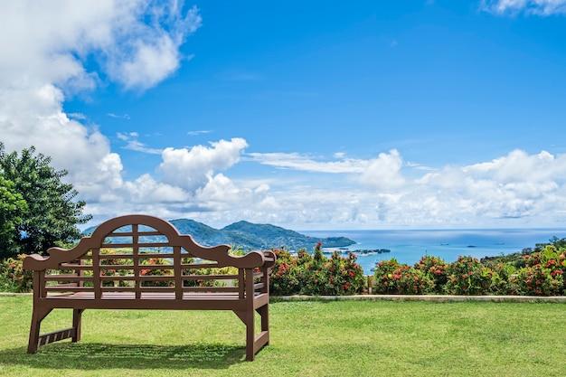 Banco de madeira na grama verde com vista tropical espetacular, seychelles