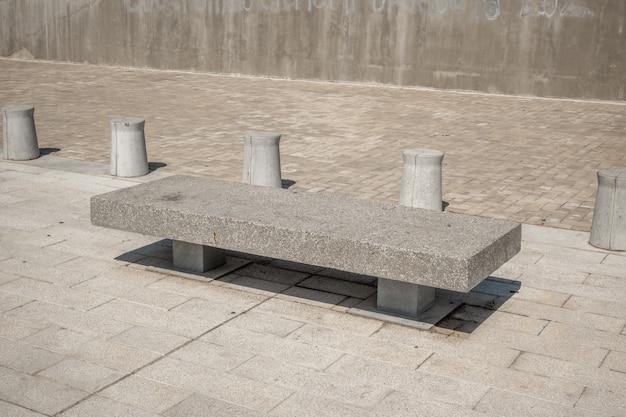 Banco de pedra coberto com lascas de mármore, cilindros de concreto no fundo do parque