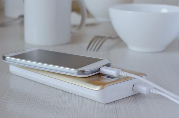 Banco de potência carrega celular na mesa da cozinha