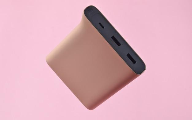Banco de potência cor de rosa pálido em um fundo rosa. bateria externa para gadgets. levitação de objetos.