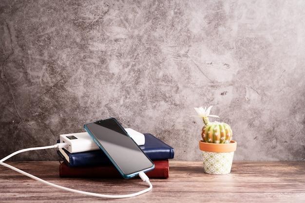 Banco de potência do carregador com smartphone no local de trabalho