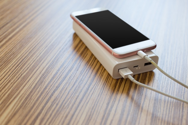 Banco de potência e celular na mesa de madeira