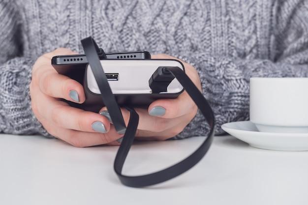 Banco de potência e smartphone em close-up de mãos femininas.