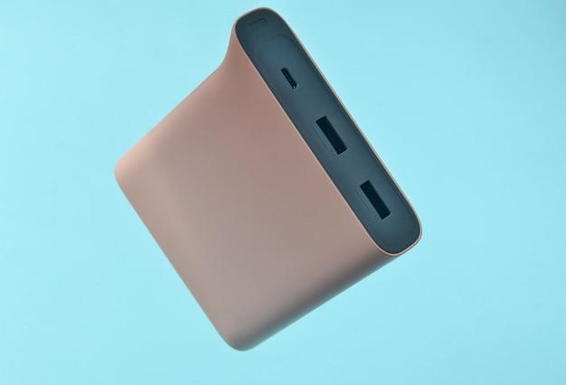 Banco de potência pálido - cor rosa sobre fundo azul. bateria externa para gadgets. levitação de objetos.