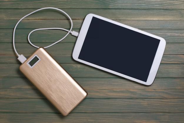 Banco de potência portátil e tablet pc em fundo de madeira