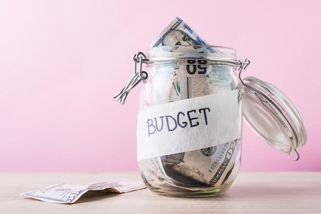 Banco de poupança de vidro com notas de dólar e orçamento de inscrição em um fundo rosa