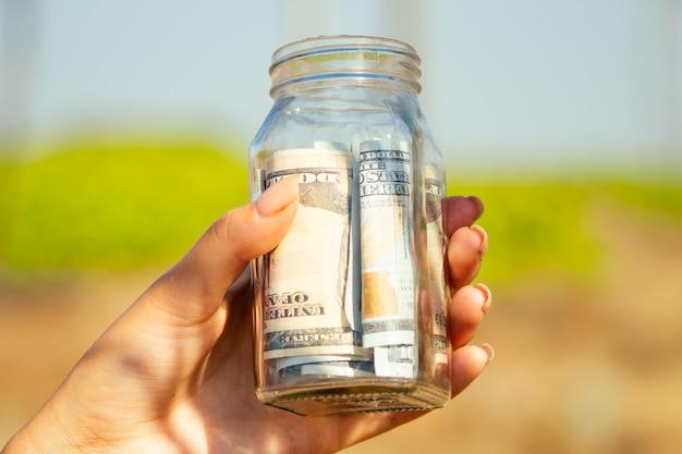 Banco de vidro com contas (dinheiro) nas mãos sobre um fundo verde