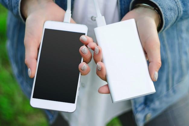 Banco do poder da terra arrendada da menina e um telefone esperto. garota carrega seu smartphone usando o banco de potência.