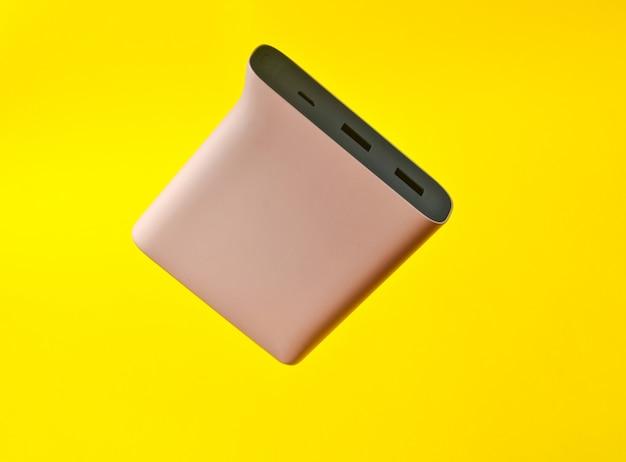 Banco do poder pálido - cor rosa em um fundo amarelo. bateria externa para gadgets. levitação de objetos.