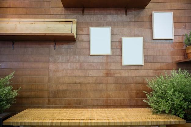 Banco do rattan contra a parede de madeira com molduras para retrato e prateleira em branco.