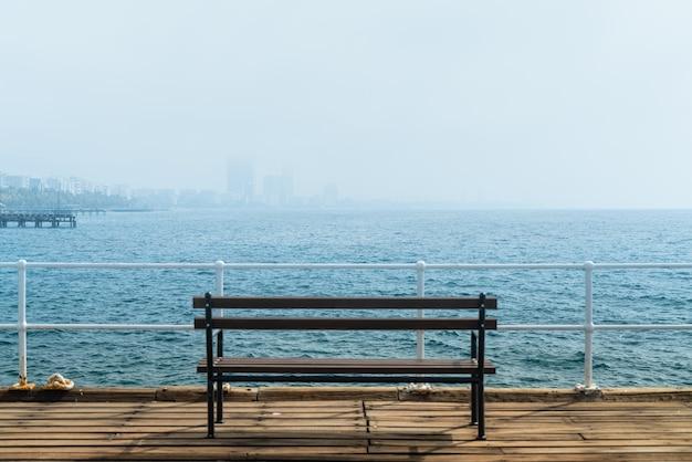 Banco em um píer com vista sobre a névoa matinal sobre o porto de limassol, chipre.
