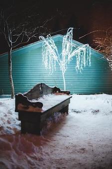 Banco marrom coberto de neve ao lado da casa