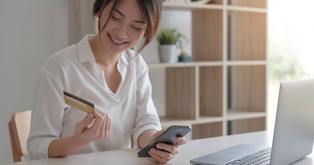 Banco móvel, compras on-line, banco digital, conceito de pagamento pela internet. mão de uma mulher usando pagamentos por telefone celular inteligente e cartão de crédito para fazer compras online